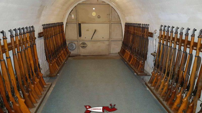 Des fusils en bois rangés le long d'un couloir.