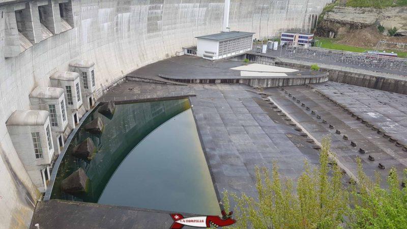 Le pied du barrage de Schiffenen. En haut à gauche, le déversoir de crue, en bas à gauche les vannes de fond et au milieu en haut, le bâtiment hébergeant les turbines.