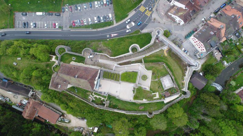 Vue d'avion du château de Valangin avec les remparts bien visibles. A droite de la photo, le village de Valangin et à gauche le parking.