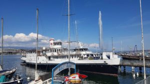 A boat moored at the Geneva harbour near the Geneva's jet d'eau