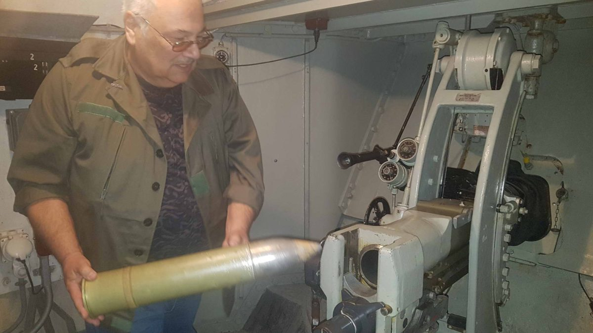 Une guide expliquant le mode de fonctionnement d'un canon avec l'introduction d'un obus fictif dans l'arme.