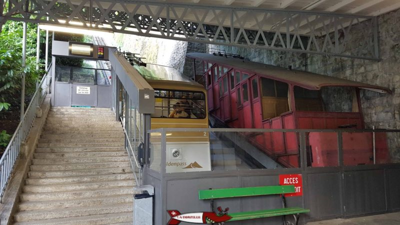 A new carriage in the golden colours of the Goldenpass next to a very old carriage used in the early days of operation.
