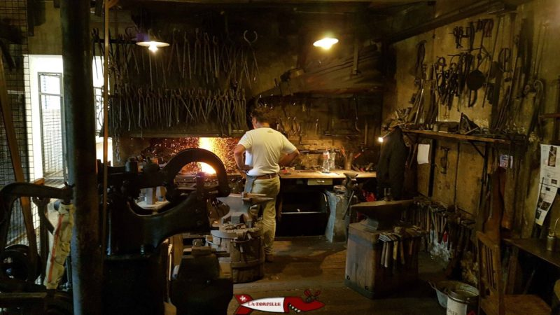 A blacksmith at the Iron and Railway Museum in Vallorbe. Water drives the hammer of the forge.