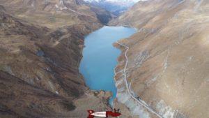 Vue aérienne du lac formé par le barrage de Moiry avec la route et le sentier pour faire le tour du lac.