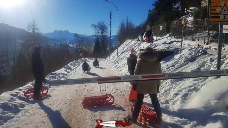 The start of the Sonloup toboggan run on the snow-covered road.