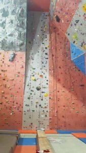 Un mur de mur de grimpe d'un peu plus de 10 mètres de hauteur avec un enrouleur et des cordes préinstallées à laniac Escalade Bulle