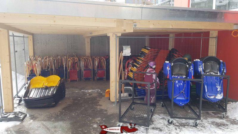 Les luges à l tzoumaz disponible à la location avec par exemple un modèle biplace. Un enfant en violet avec l'équipement nécessaire. Boot, pantalons et veste de ski, casque, gants, lunettes et écharpe.