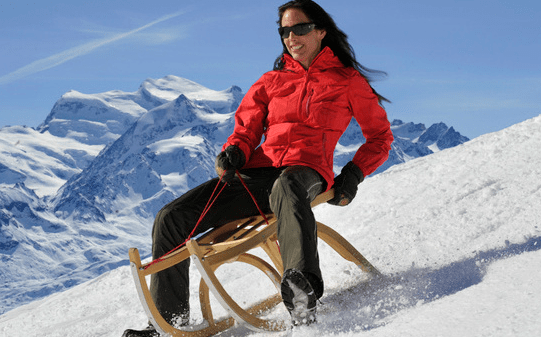 A photo from Switzerland Tourism that does not show the example with a sledder not wearing a helmet or even a hat, but with a nice view of the Grand Combin. See tips for safe sledging.