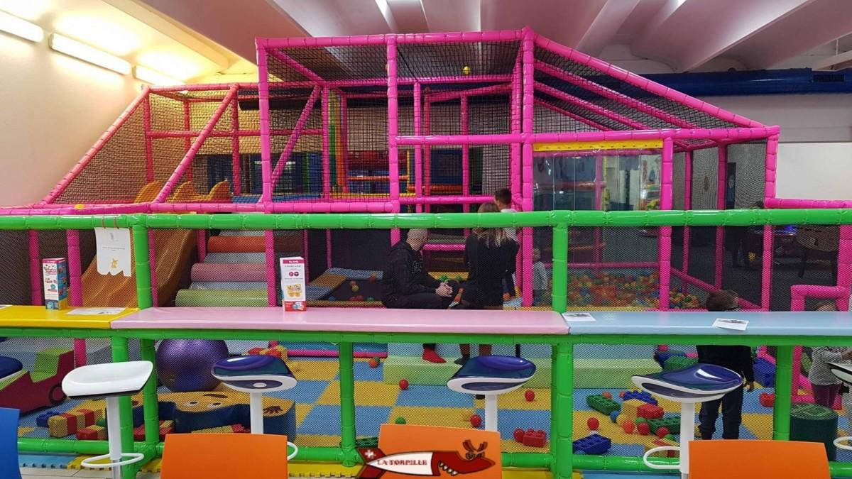 Un structure tubulaire avec boules en plastique, toboggans et autres petits jeux à côté de la cafeteria.