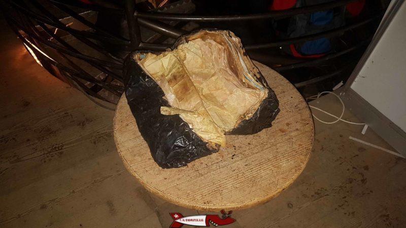 L'emballage en papier ayant contenu le jambon cuit dans l'asphalte.
