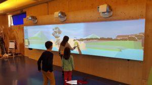 Des enfants jouant avec le mur tactile à la maison de la rivière