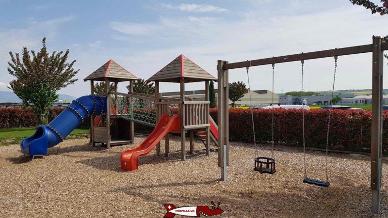 En extérieur de la salle d'urba kids, se trouve une place de jeux avec des tables.