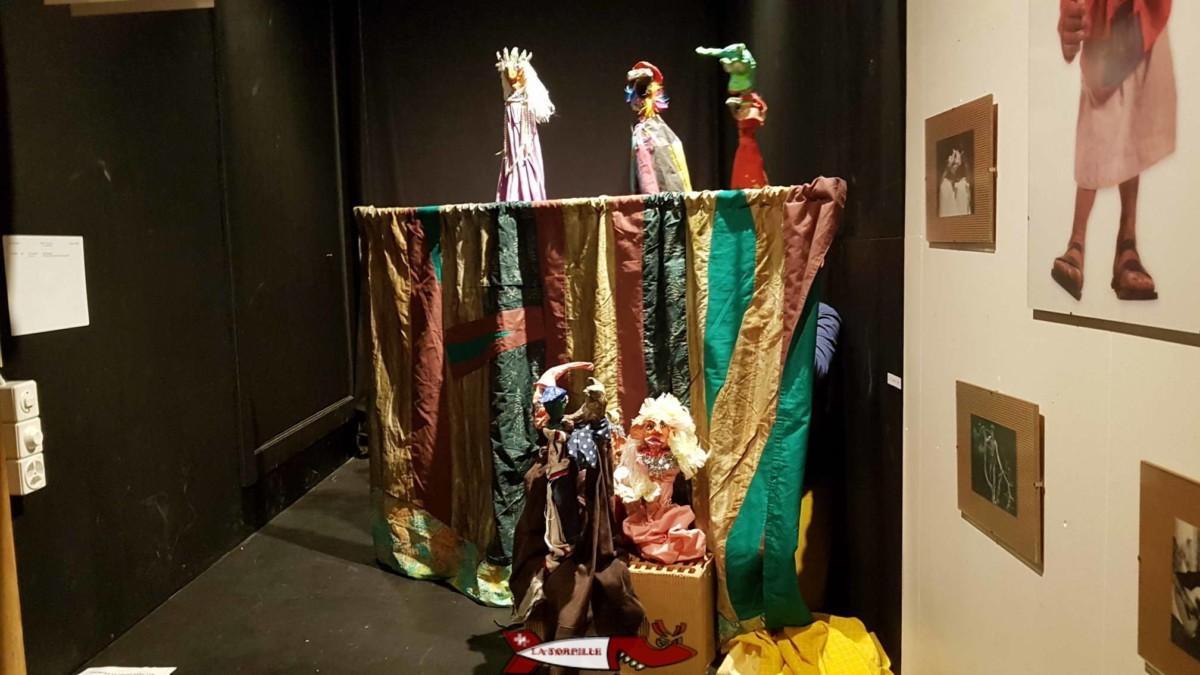 Le théâtre avec des enfants cachés derrière le rideau en train de manipuler de marionettes.