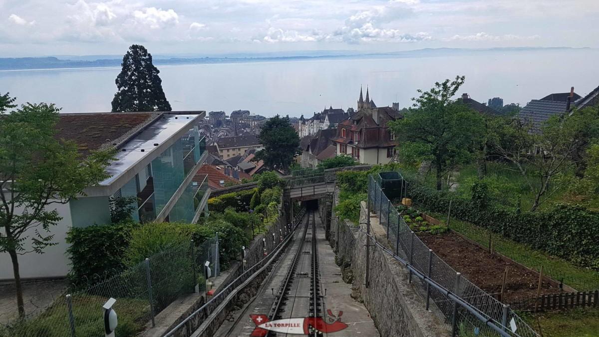 La vue depuis la gare de Plan à neuchâtel. On peut voir le château en blanc et les deux tours de la collégiale.
