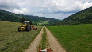 le chemin en terre en direction des gorges de covatannaz - un tracteur coupant l'herbe dans un champs