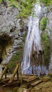 La cascade de Môtiers avec l'entrée de la grotte de Môtiers sur la gauche au début du parcours des gorges de la Poëta-Raisse