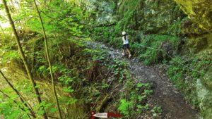 La Torpille marchant le long d'un sentier sécurisé avec une corde métallique en raison de la forte pente sur le côté sur le parcours des gorges de la Poëta-Raisse