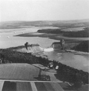 "The Möhne dam near Dortmund was bombed by the Royal Air Force in 1943 during Operation Chastise. The picture was taken from an English plane. New bombs called ""bouncing bombs"" must be invented to destroy the dams and pass over the anti-torpedo protection nets."