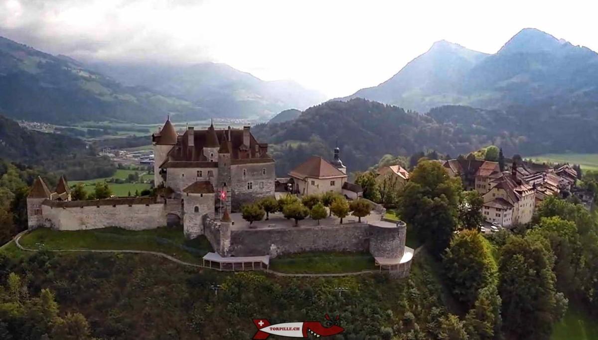 Un magnifique cadre naturel verdoyant dans le lequel se trouve le vieille ville et le château de Gruyère sur un éperon rocheux