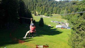 Deux enfants s'élancent sur la première tyrolienne dans l'espace loisirs Basseruche
