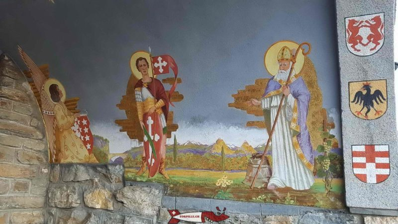 The paintings and badges on the porch of the chapel under the statue of Christ the King