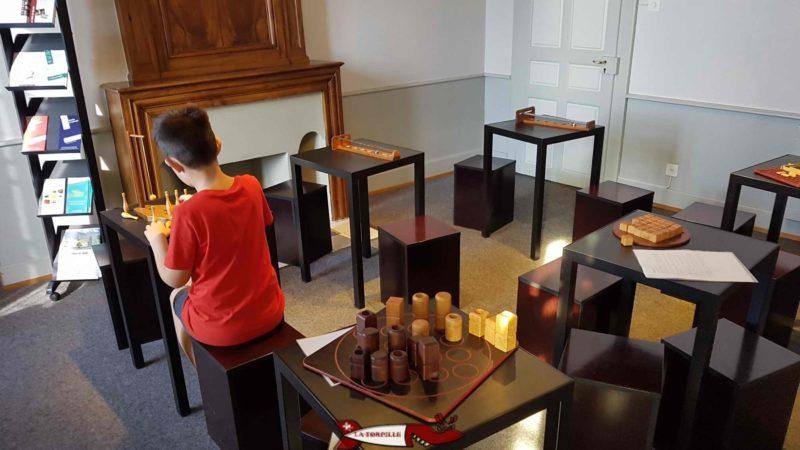 Un enfant ;-) au prise avec un jeu d'agilité au musée suisse du jeu