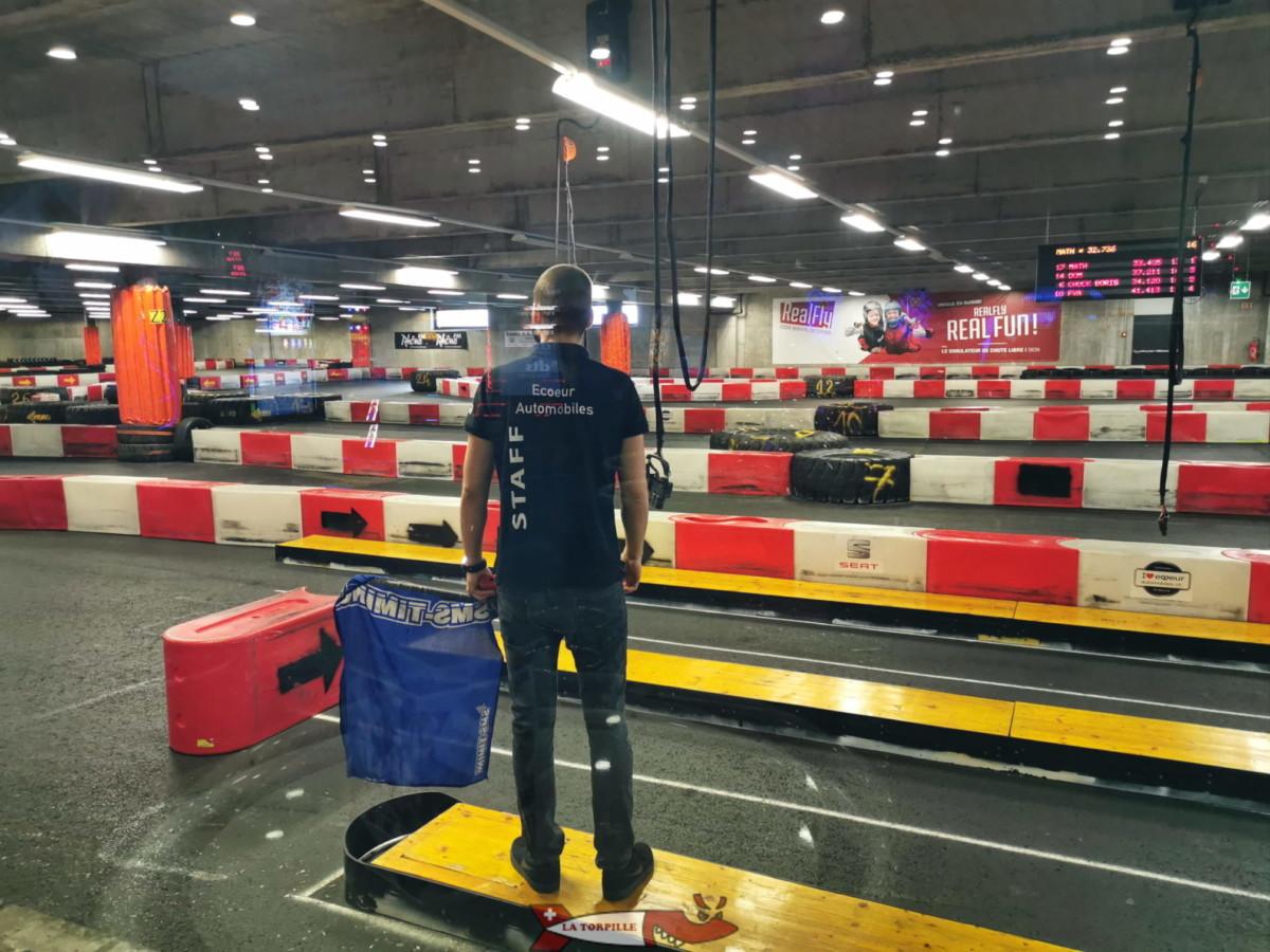 Un surveillant avec un drapeau bleu au Funplanet de Villeneuve. Ce drapeau est le plus utilisé dans le karting de loisir.