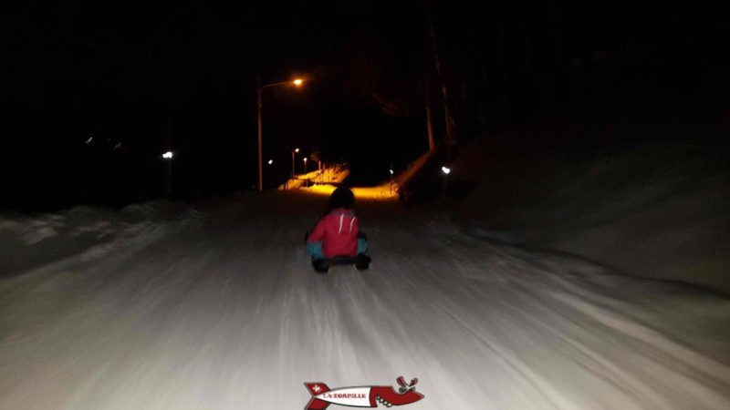 The sled run at night partially illuminated by the road lights.