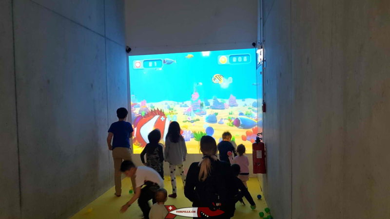 Children throwing balls at fish posted on the touch wall at Kids Fun Park Etoy