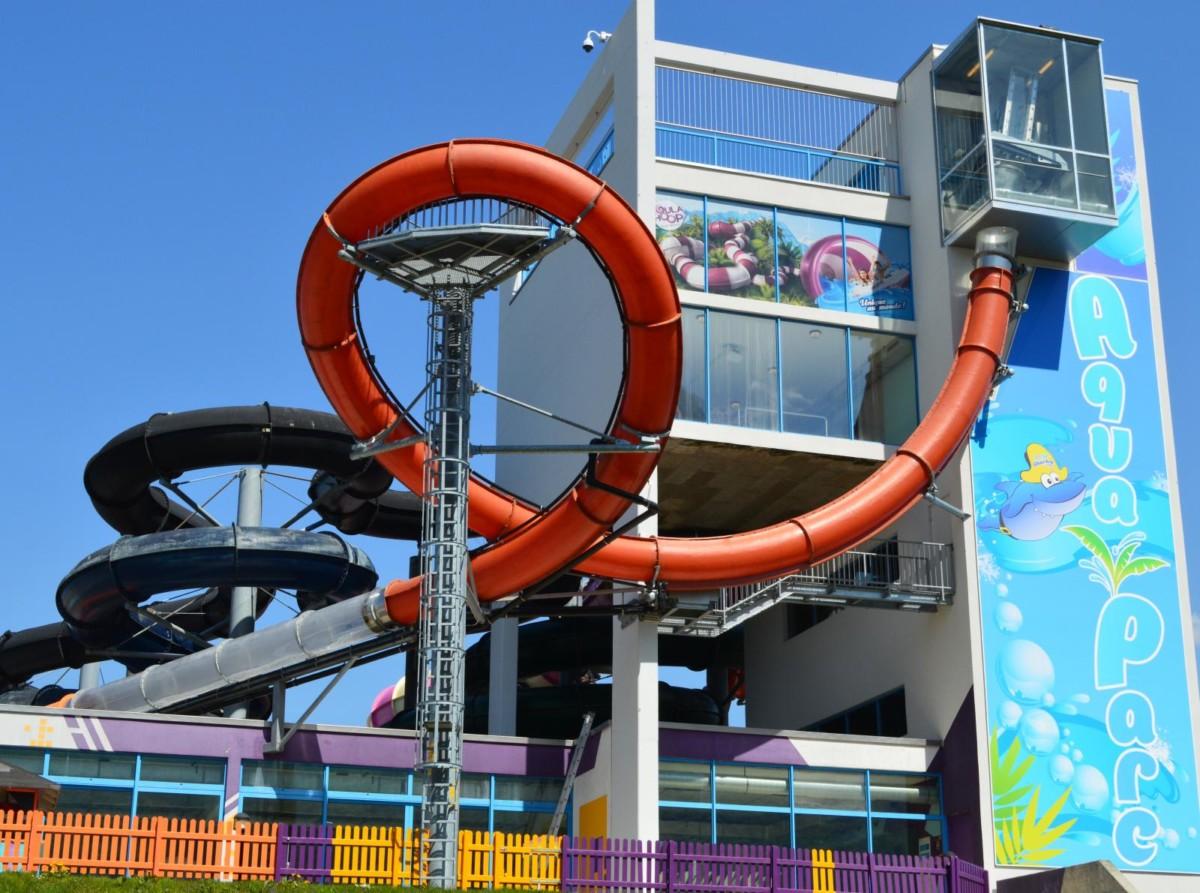 Le Booster Loop d'Aquaparc en orange avec le sas vitré de départ en haut à droite.