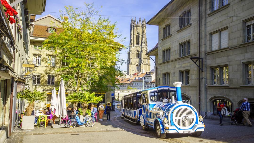 Le petit train de Fribourg avec la cathédrale en arrière-plan.