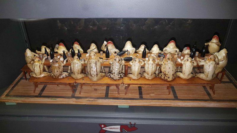 Des grenouilles présentées attablées en train de prendre un repas.
