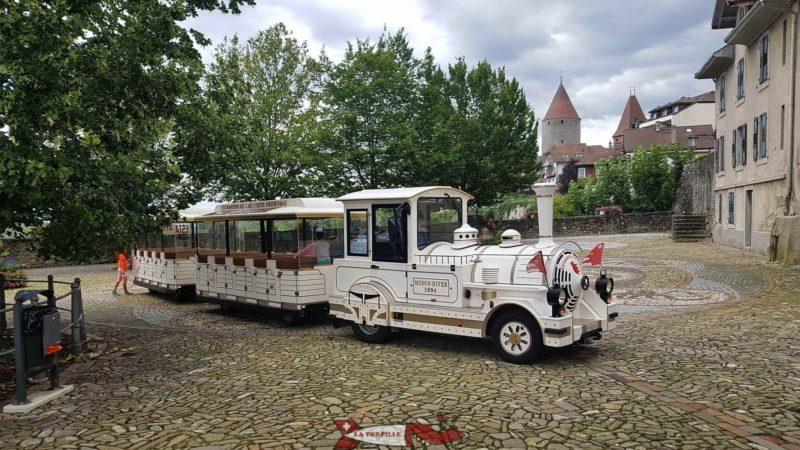 Petit train d'Estavayer-le-Lac en pause à la place de Moudon. En arrière-plan, le château de Chenaux.