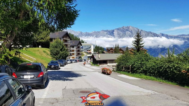 Les places de parking le long de la route à la Tzoumaz avec le départ du télécabine en arrière-plan.