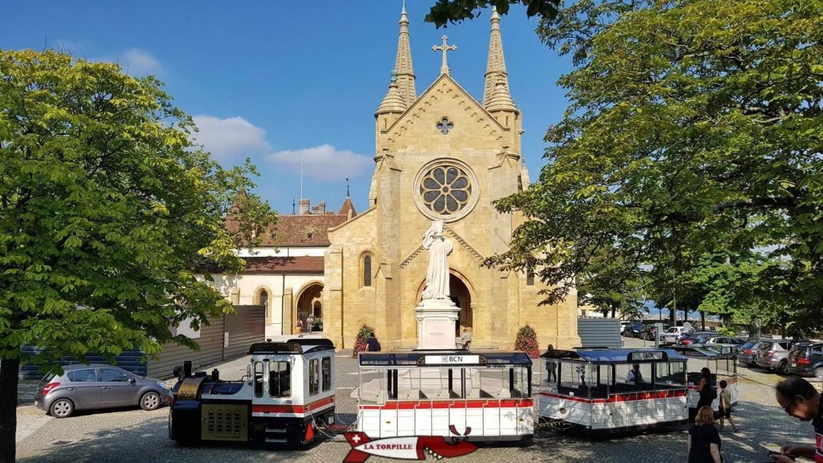 L'église réformée et collégiale de Neuchâtel à côté du château avec le petit train et la statue blanche du Réformateur Guillaume Farel.