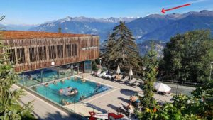 The outdoor area of the baths with the Weisshorn in the background at an altitude of more than 4500 metres (red arrow).