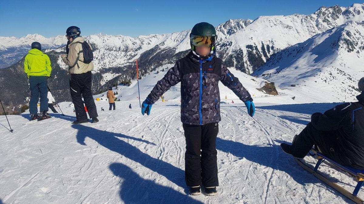 Un enfant correctement équipé pour la pratique de la luge avec un casque à lunettes incorporées, des gants de ski, un pantalon et une veste de ski, des boots de neige.