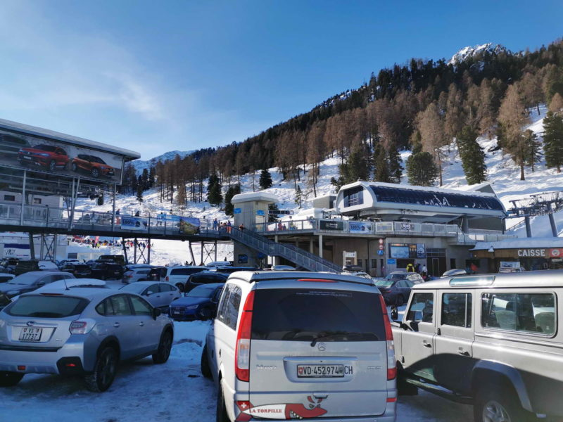 The car park with the departure platform of the Siviez ski lifts in the background.