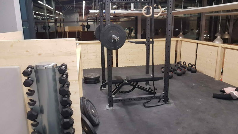 Above the cafeteria is a weight bench with dumbbells.