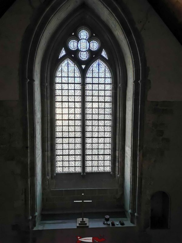 The large stained glass window of the chapel visible from the outside.