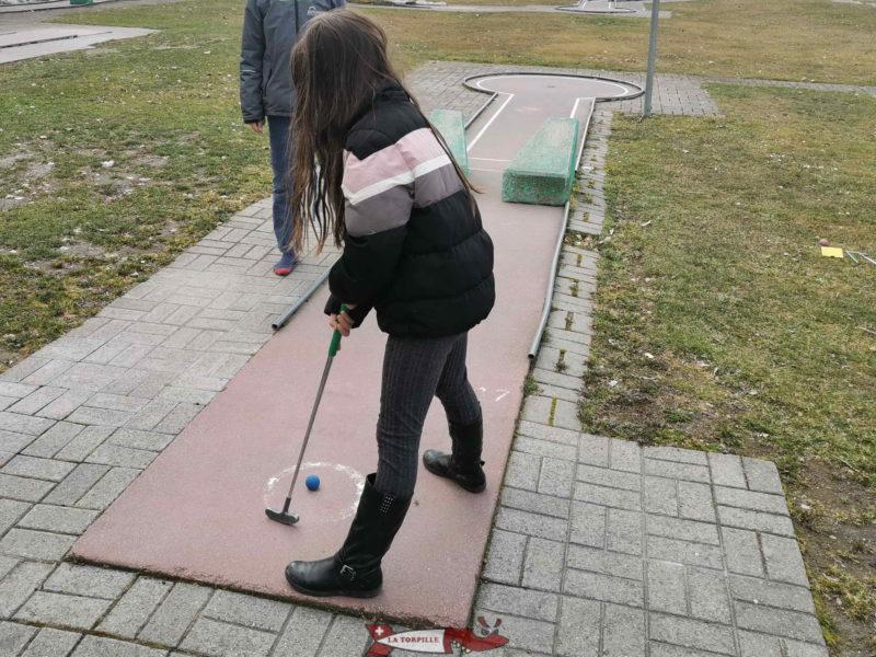 Une joueuse sur une piste de minigolf.