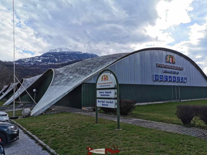 Le parking se trouve le long de la route principale à côté du bâtiment des tennis. domaine des iles de Sion.