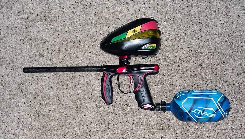 Un pistolet à air-comprimé pour le paintball. La partie bleue contient l'air comprimé et la contenant noir, les billes de peinture.