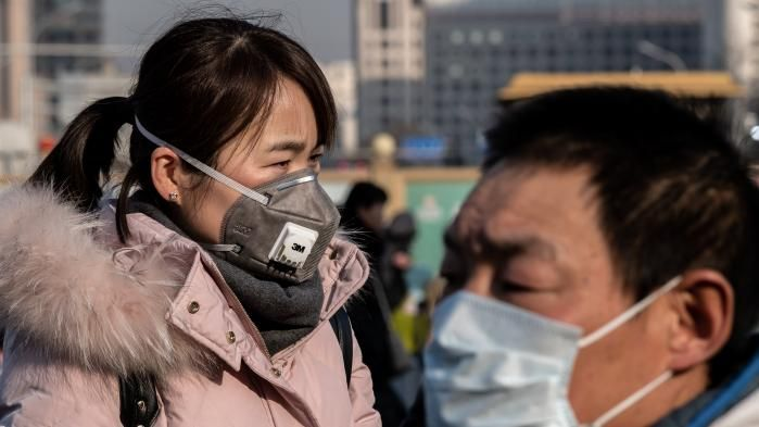 Two people wearing masks. On the left an FFP2 mask. On the right, a surgical type mask.