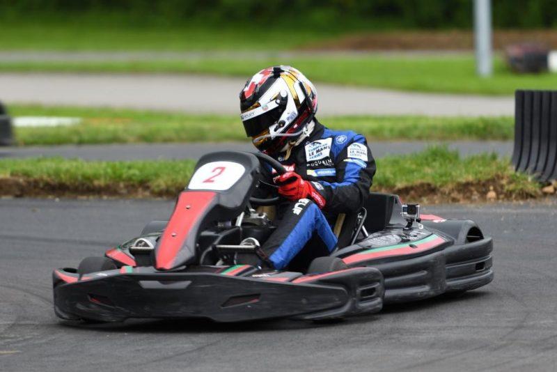 Un pilote de karting équipé d'un casque, d'une combinaison et de gants.