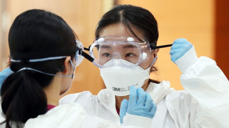 Medical workers putting on their coronavirus protective clothing with mask, goggles and gloves.