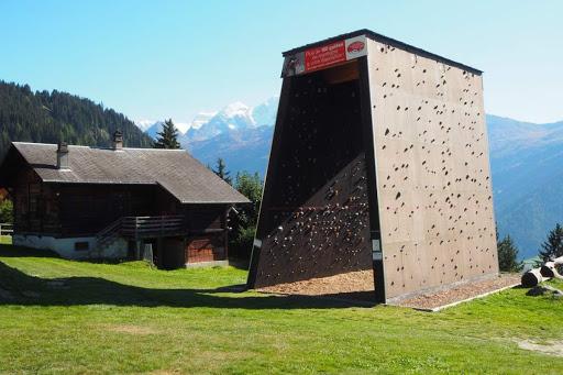 La place de jeux avec le mur de grimpe.
