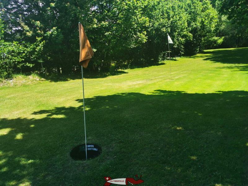 Un parcours où on peut voir deux drapeau de trou. L'orange pour le Footgolf et le blanc pour le Swin Golf.
