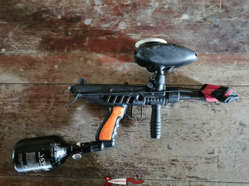 Lanceur le plus utilisé dans pratique de loisirs du paintball. La bouteille d'air comprimé se trouve sur la gauche de la photo et, sur le haut, se trouve le réservoir de bille du lanceur.