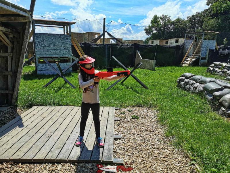 Un enfant équipé d'un lanceur de paintball. Il faut tirer et pousser sur la partie noir sous le canon pour réarmer le lanceur.
